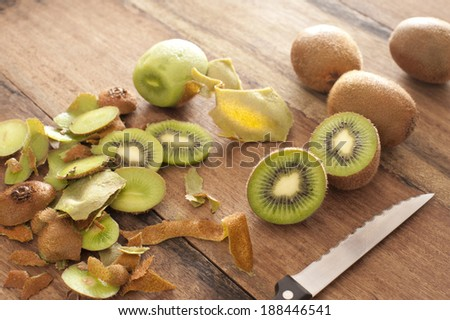 Peeling and slicing fresh tropical kiwifruit for dessert with whole and halved fruit and peels lying on a wooden kitchen counter with a knife - stock photo