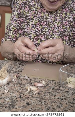 peeling garlic - stock photo