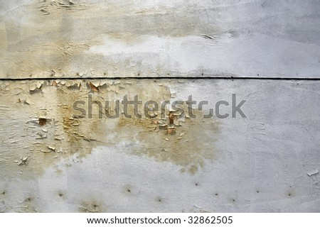 Peeling paint, mold growth and water stains on the ceiling of an abandoned house. - stock photo