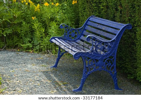 Peeling paint on an old blue garden seat adds a whimsical touch to the garden