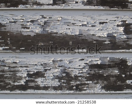 Peeling paint on the siding of a building - stock photo