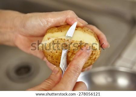 Peeling potato. shallow depth of field - stock photo
