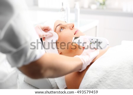 Peeling, ultrasound, woman at vanity. The woman's face during a facial at a beauty salon