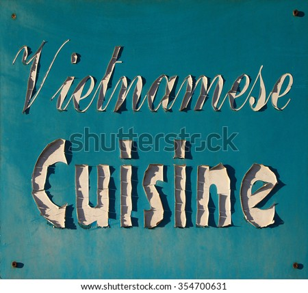 """Peeling """"Vietnamese Cuisine"""" sign in sunlight with shadows  - stock photo"""