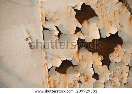 Peeling white paint and rust on the hull of an old fishing trawler - stock photo