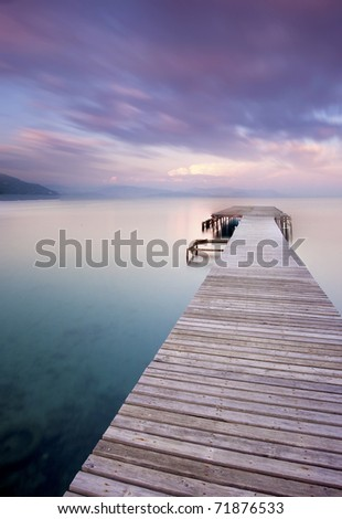 Peer at the beach leading into the ocean at sunset - stock photo