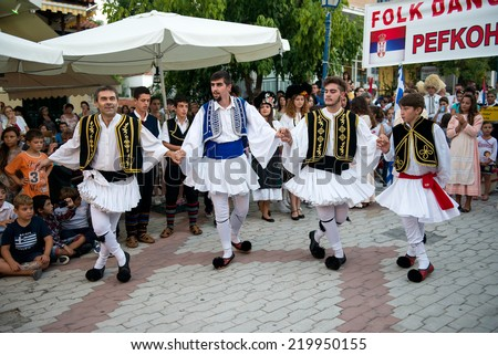 PEFKOHORI , GREECE - SEPTEMBER 19 2014 : Folk Dancers from several countries   dance in the Annual Folk Dance festival in the village square of Pefkohori ,Greece.The Greek dancers perform their dance. - stock photo