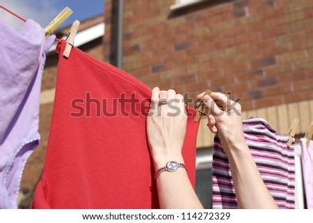 Pegging out washing to dry on clothes line - stock photo