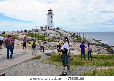 PEGGY'S COVE, NS, CANADA - AUG 2, 2016: An unidentified bagpiper plays for tourists near the lighthouse at the popular tourist destination of Peggy's Cove, Nova Scotia.