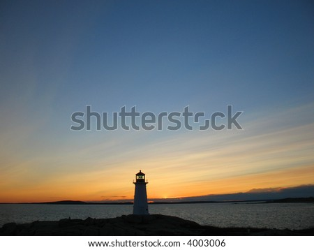 Peggys Cove lighthouse with big sky at dusk - stock photo