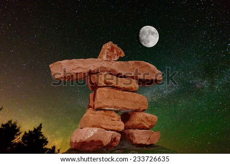 PEI Red Sand Stone inukshuk against milky way and moon - stock photo