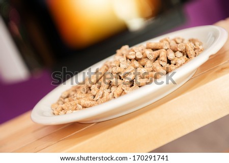 pellet stove with wood pellets on foreground - stock photo