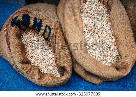 Pellets compressed organic matter, or biomass made from sawdust in their organic bags next to eachother - stock photo
