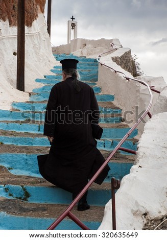 PELOPONNESE, GREECE - OCTOBER 11, 2005: An unidentified Greek-Orthodox priest leaves a monastery after celebrating Mass. Economic crisis upgraded even more the role of the Church in Greece. - stock photo