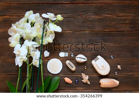 Pemza to clean up old leather heels, electric shaver depilator on white towel with orhides and shells on dark wooden background. Spa concept.
