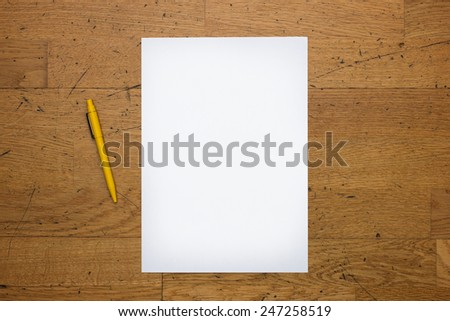 Pen and a blank white paper sheet on a worn wooden table surface, viewed from above - stock photo