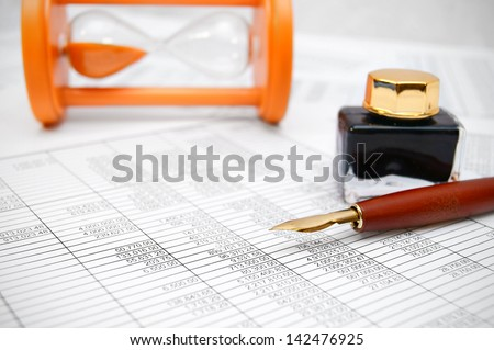 Pen and a sand-glass on documents. - stock photo