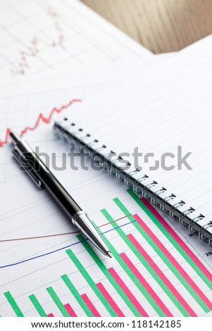 pen and blank notebook on business graph - stock photo