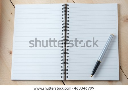 pen and book on wood background
