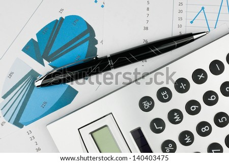 Pen and calculator on a background of diagrams can be used as background - stock photo