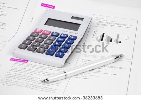 Pen and Calculator on a English Test Paper - stock photo
