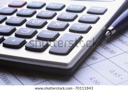 pen and calculator on business paper
