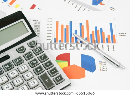 Pen and calculator on paper table with diagram - stock photo