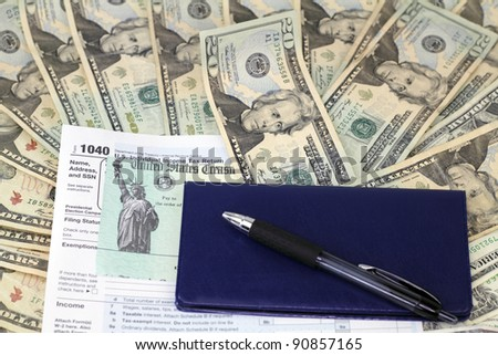 Pen and checkbook on top of tax refund check on a 1040 tax form on lots of paper cash ready to be deposited. - stock photo