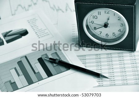 Pen and clock on a market report
