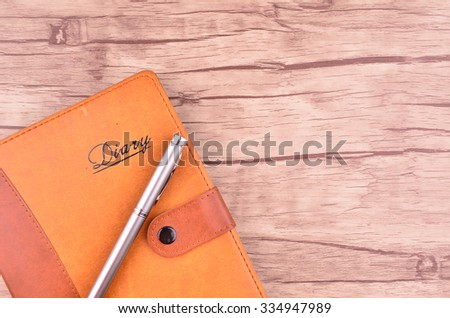 Pen and diary on wooden background - stock photo