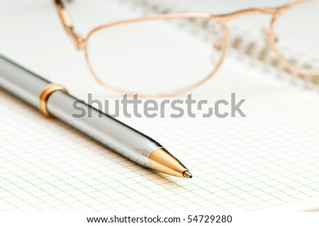 Pen and eye glasses on the page - stock photo