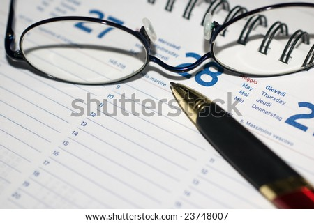 Pen and eyeglasses on agenda page with shallow depth of field, selective focus