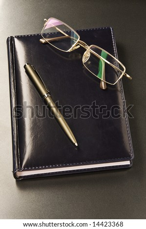 pen and glasses lay on a black leather organizer - stock photo
