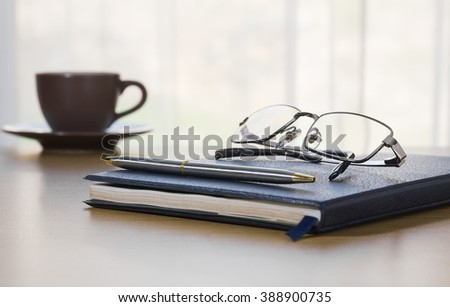 Pen and Glasses on a book with on the desk by nature background - stock photo