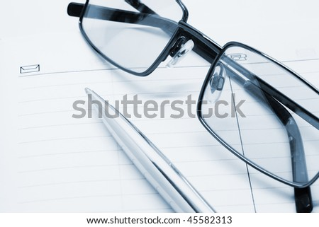 Pen and glasses on a notebook - stock photo