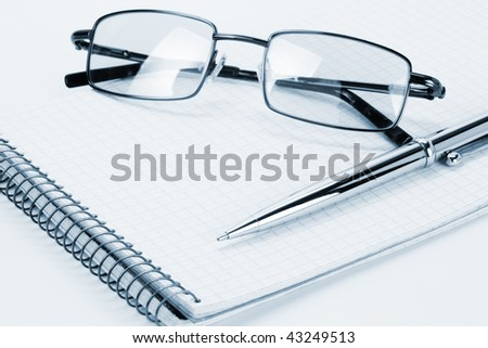 Pen and glasses on a notebook on white background - stock photo
