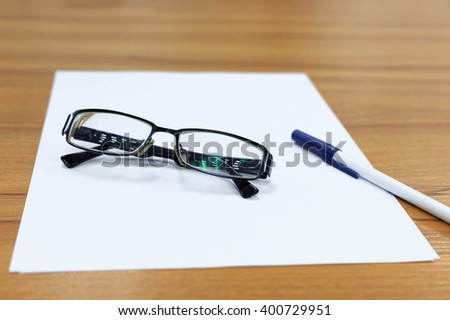 Pen and glasses on blank paper on wood table - stock photo