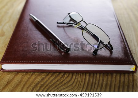 pen and glasses on notebook