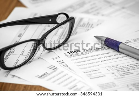 Pen and glasses on US tax form 1040. Business concept
