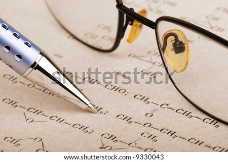 pen and glasses over a chemistry sheet - stock photo