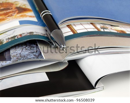 Pen and magazines.  Many colour magazines with pen on top - stock photo