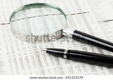 Pen, and magnifier rest on stock price detail financial newspaper