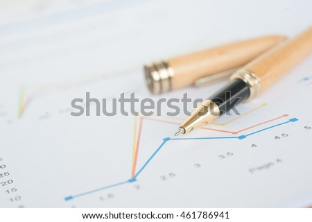 pen and marketing statistic with money graph