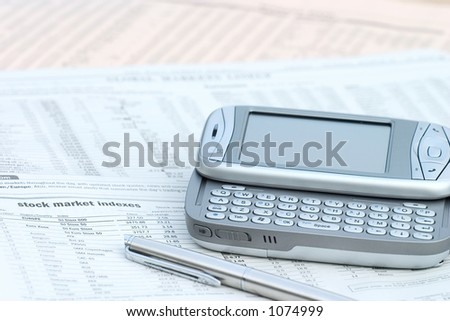 pen and mobile phone on top of a financial newspaper. - stock photo