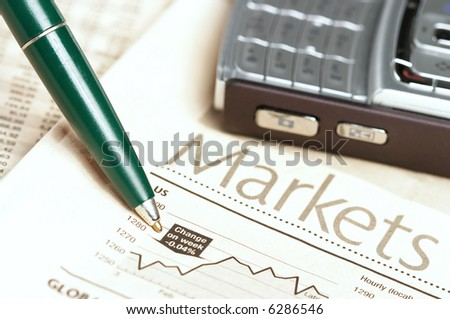 Pen and mobile phone on top of a financial newspaper - stock photo