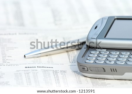 Pen and mobile phone on top of financial newspaper. - stock photo