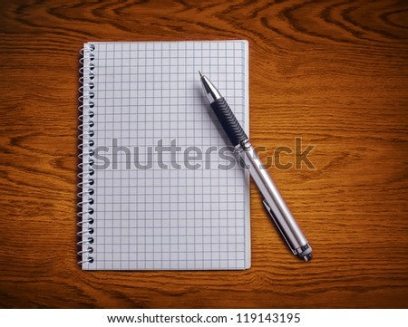 Pen and notebook on a wooden table.