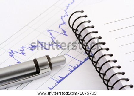 pen and notebook on stock chart - stock photo