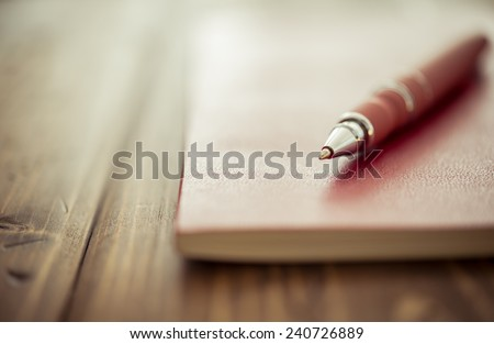Pen and notebook up close on a rustic wooden desk - stock photo