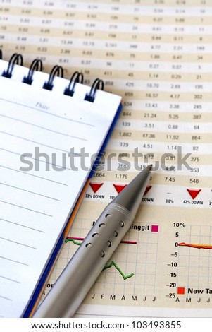 Pen and notepad on financial report for business concept - stock photo